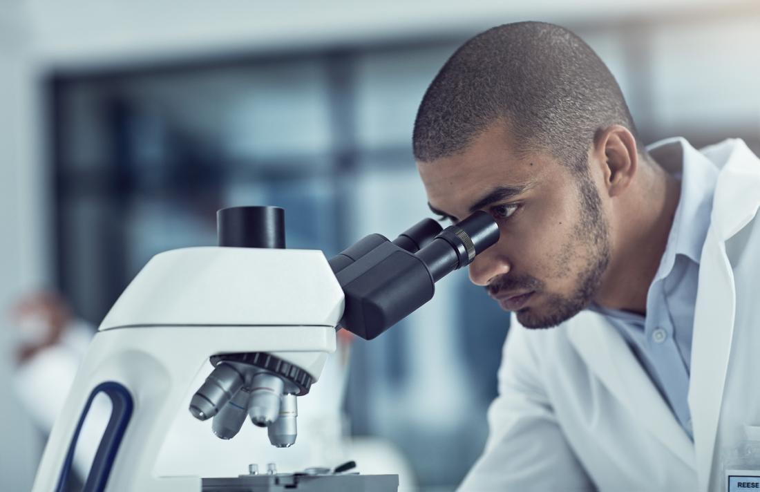 Lab tech examinant les lames sous un microscope.
