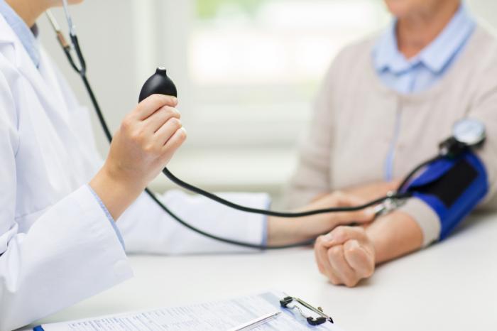 um médico medindo a pressão arterial de adultos mais velhos