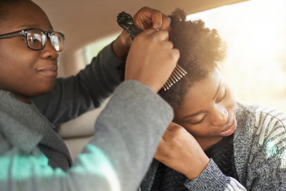 Deux femmes noires coiffant les cheveux les uns des autres.