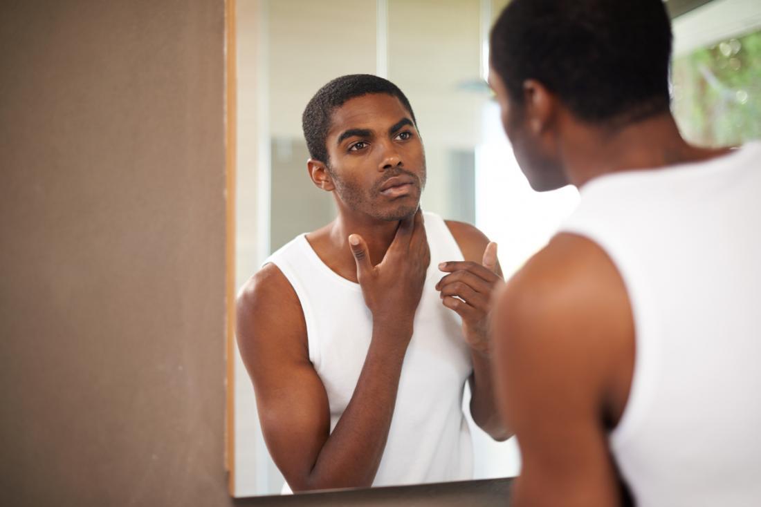 Човек пред огледалото, инспектиращ лицето и овлажнява кожата.