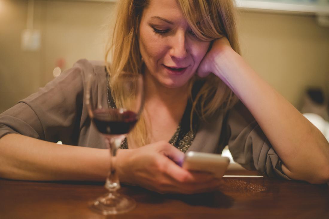 kobieta trzyma telefon z kieliszek czerwonego wina na stole
