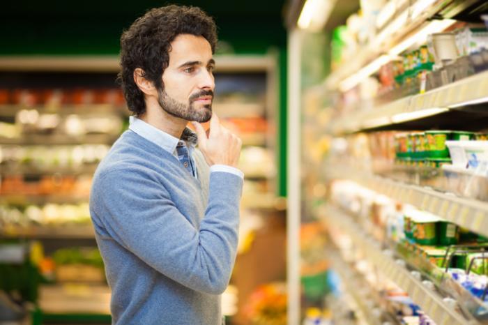 [Mann erwägt seine Möglichkeiten im Supermarkt, indem er sein Kinn streichelt]
