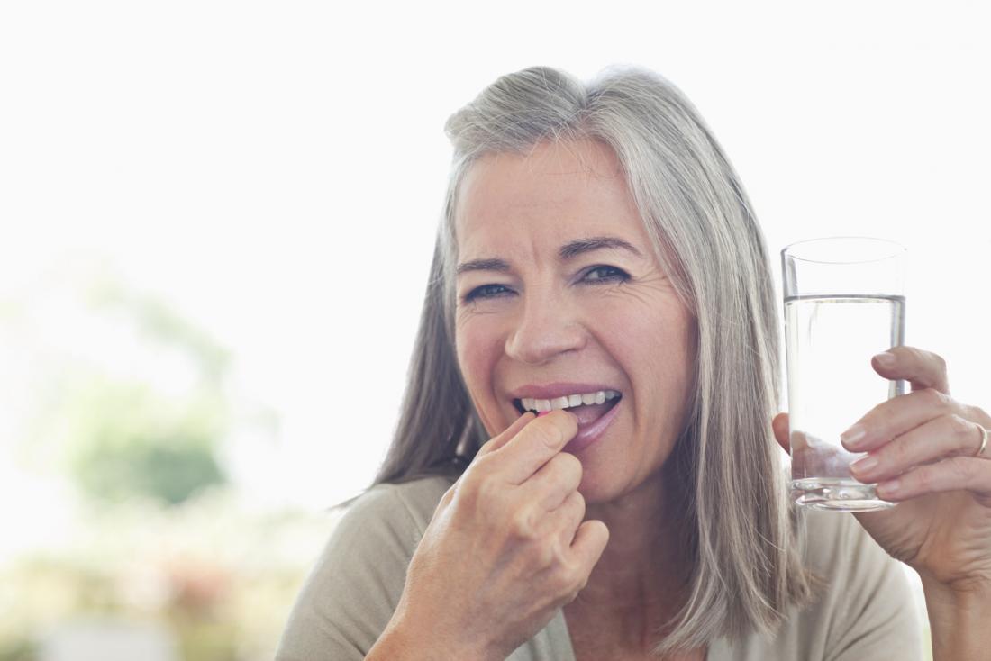 Signora anziana che prende la pillola