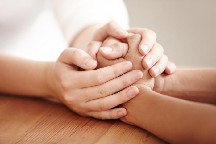 Dwie osoby trzymające się za ręce