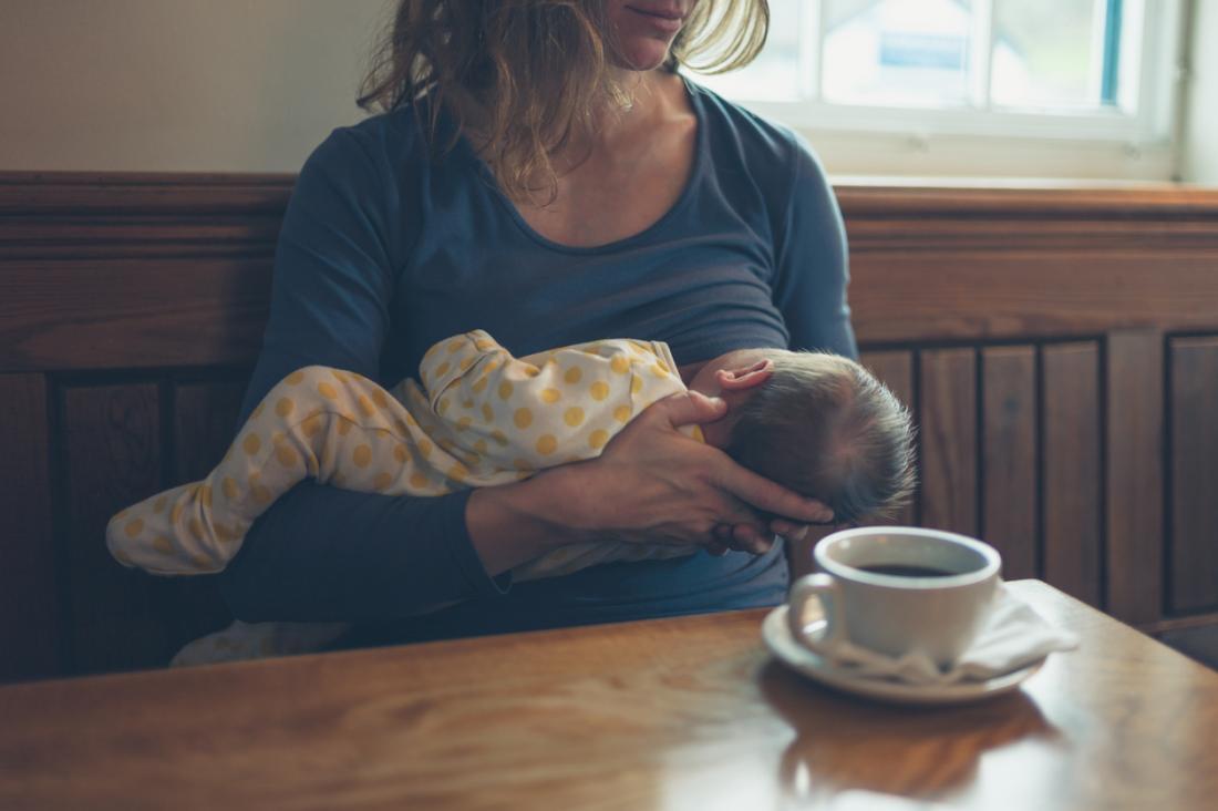 Người phụ nữ cho con bú một em bé trong quán cà phê trong khi uống cà phê.