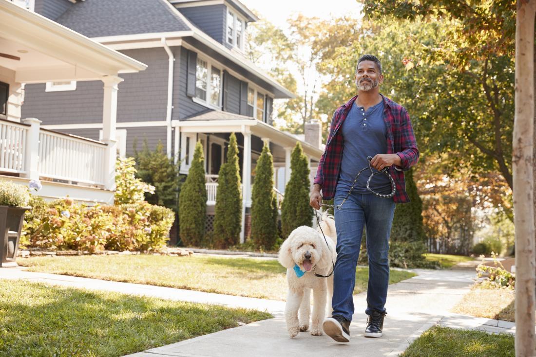 Người đàn ông bên ngoài trên con chó đi bộ đường phố.