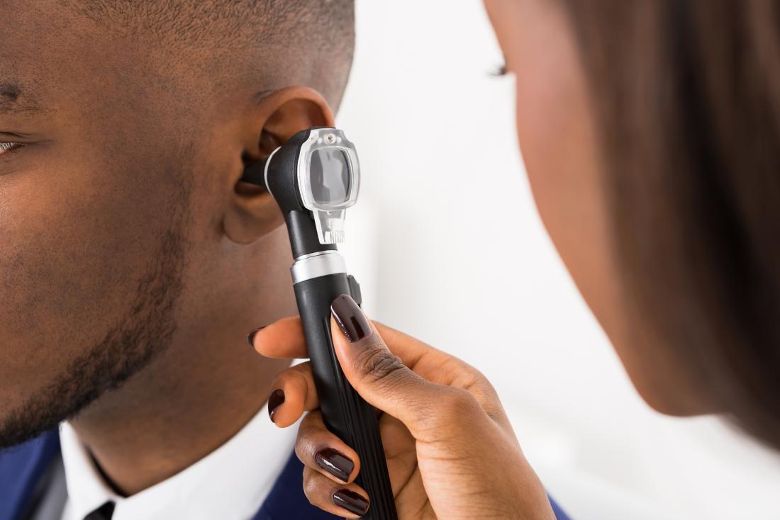 医者は患者の耳を検査する。