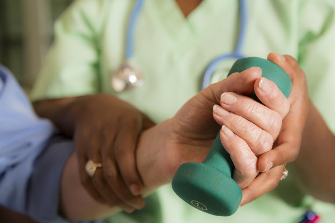 Fisioterapia levantando um peso para melhorar a força e o controle da mão.