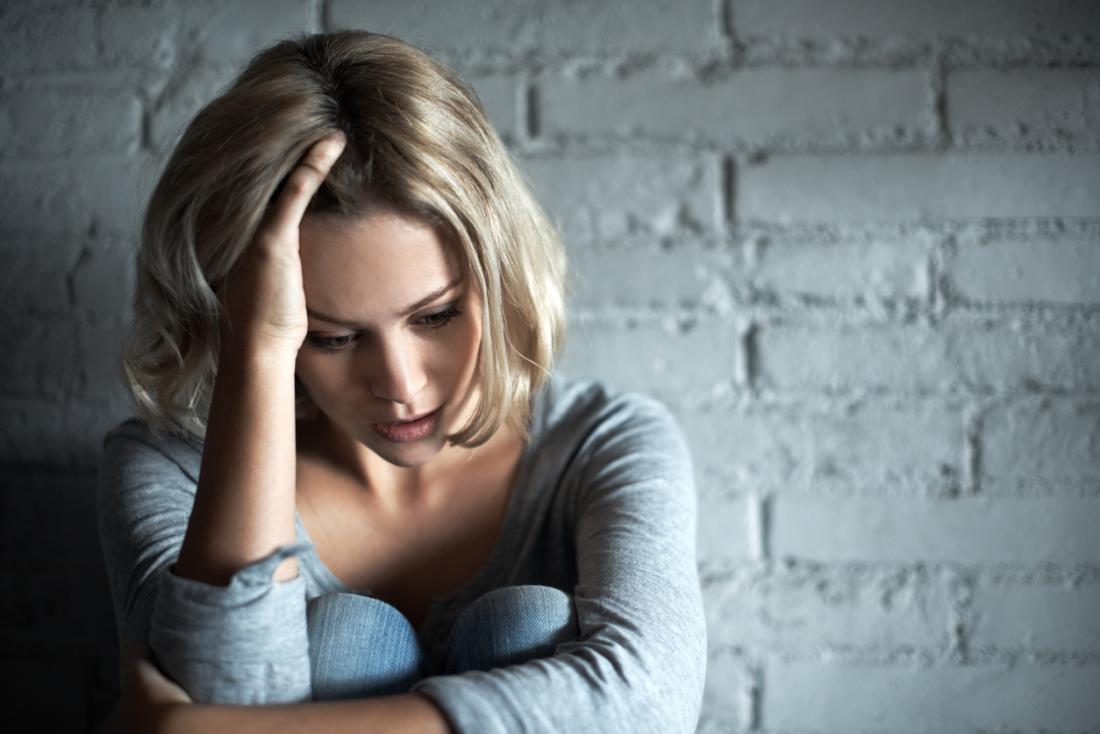 うつ病の女性、壁に座って手をつないでいる。