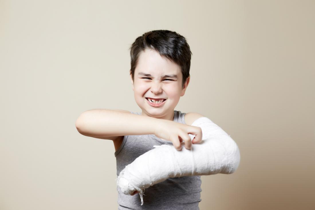 Junge mit einem juckenden Arm unter seiner Besetzung