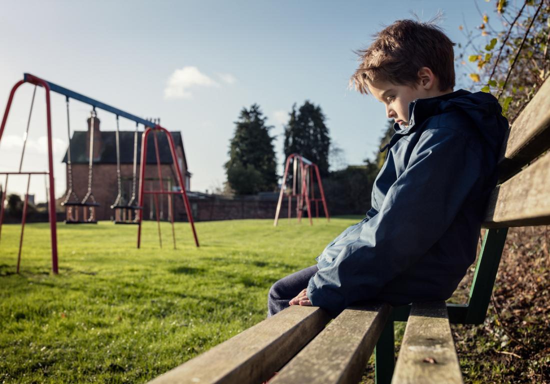 тъжно момче, седнало на пейка на детската площадка