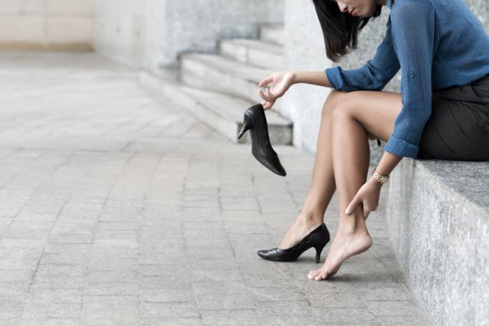 Una donna con i piedi doloranti da indossare i tacchi.