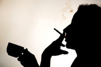 Silhouette de la personne qui fume une cigarette et tenant une tasse de café.