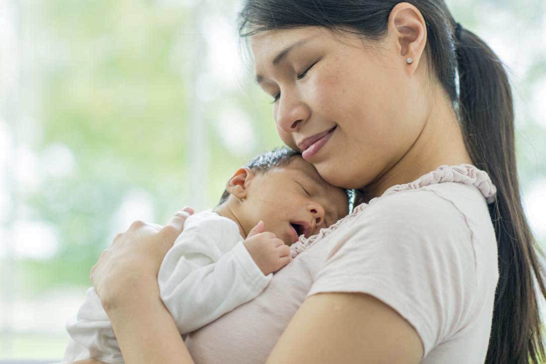 млада майка, която държи бебето си