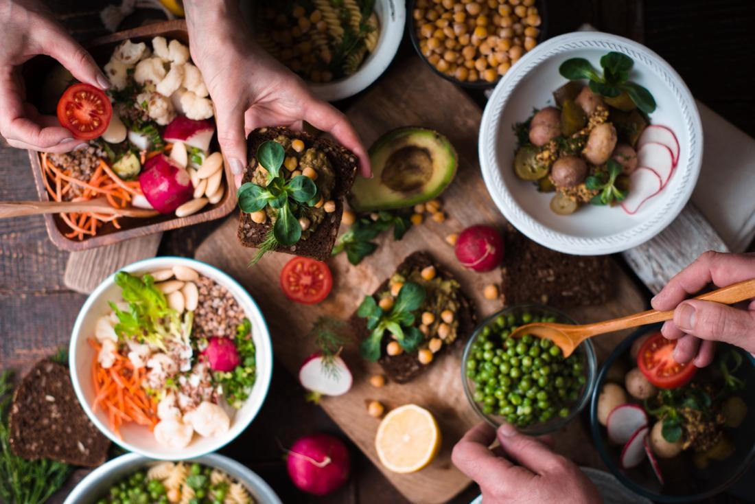 Веганска диета, състояща се от растителни храни в различни салатни чаши и на дъска за рязане.