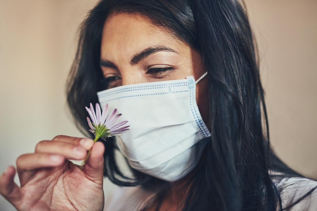Alerji maske takan ve alerjinin ateşe neden olup olmadığını merak eden çiçek tutan kadın.