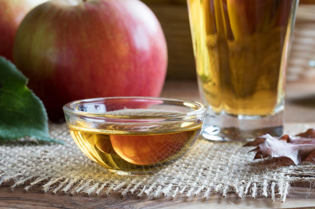 Dấm rượu táo trong thủy tinh và bát, bên cạnh táo lớn trên bàn.