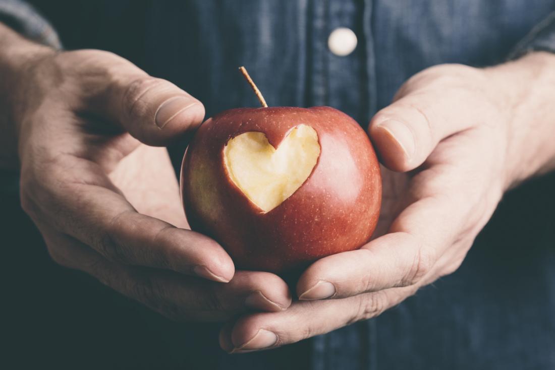 Apple bị giữ trong tay người đàn ông với hình trái tim cắt ra khỏi nó.