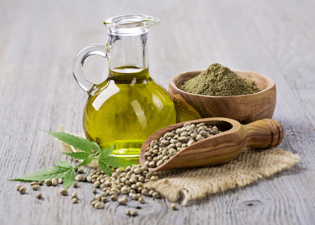 Olej marihuany CBD w małym dzbanku, obok drewnianej łyżki z nasionami konopi i drewnianej miski z marihuaną.
