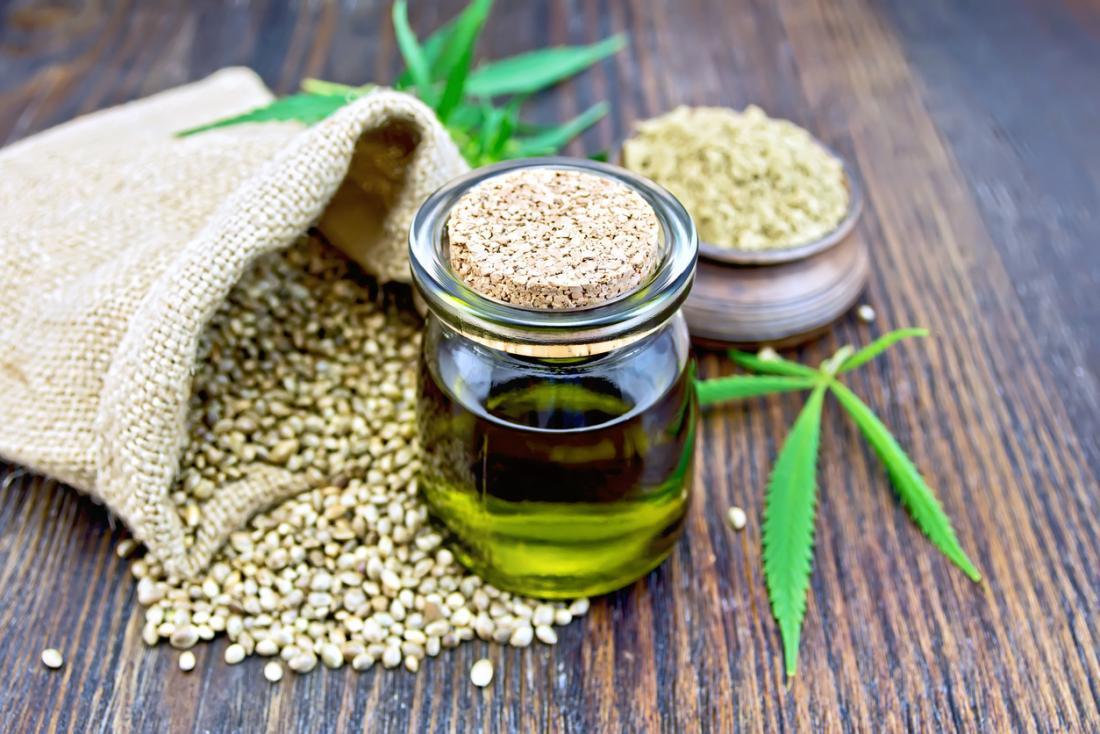Olio di canapa CBD, in vasetto trasparente con un sacchetto di semi di canapa, foglie di marijuana,