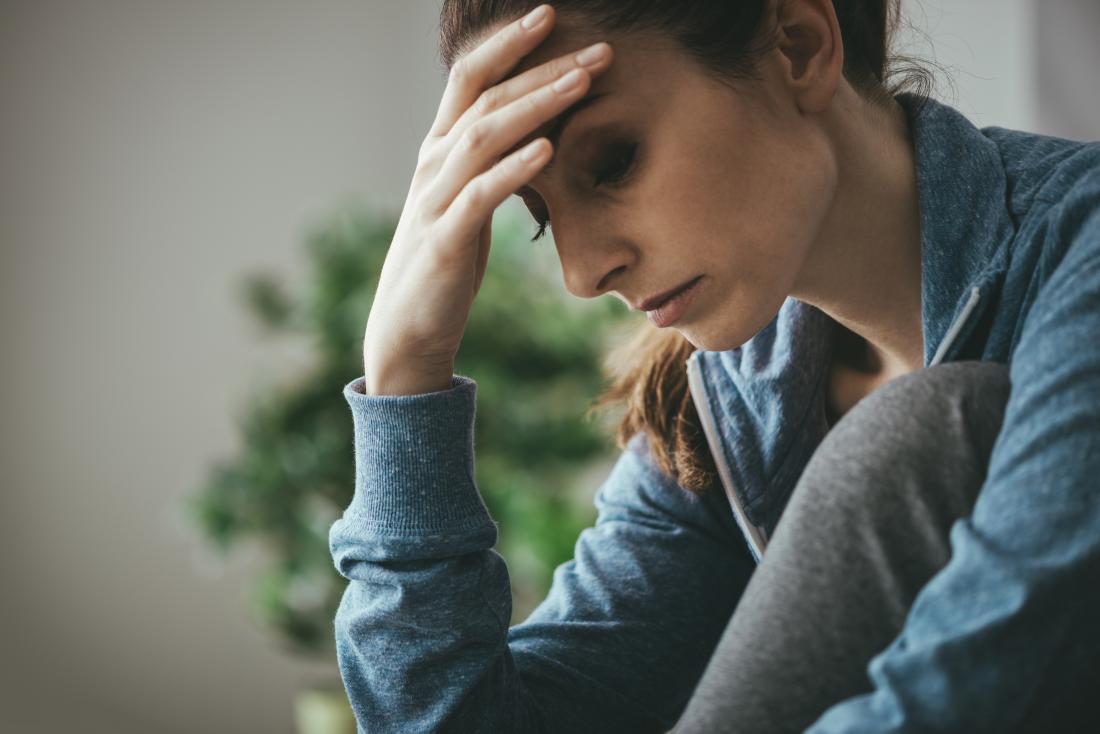 子宮内膜疲労と頭が疲れて悲しい女性。