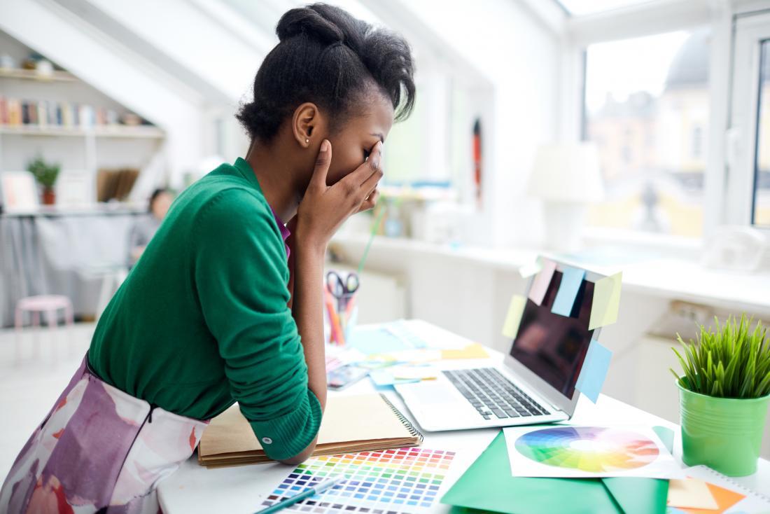 彼女は疲れているので、オフィスを擦っている机の中の女性。