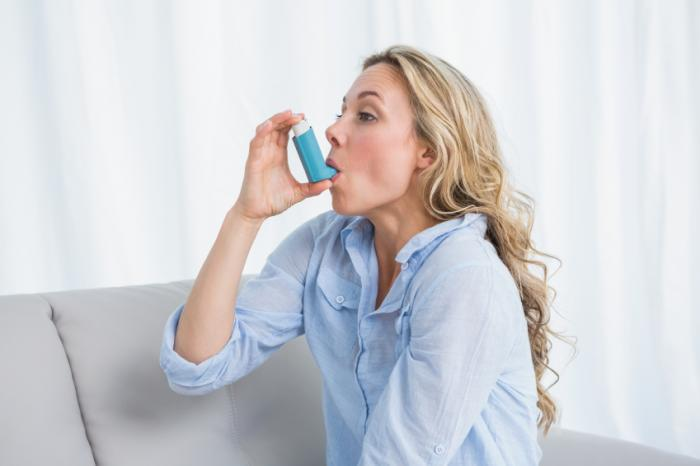 Uma mulher está usando um inalador de asma.