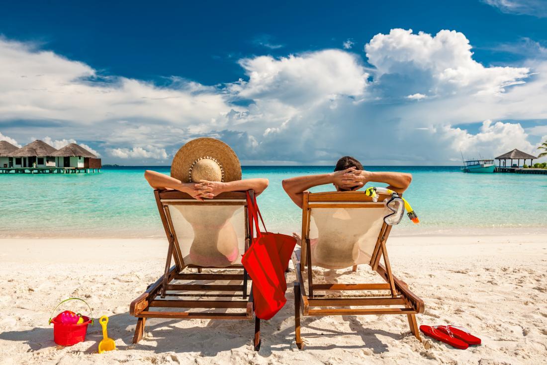 cặp đôi ngồi trên ghế xếp trên bãi biển đầy cát