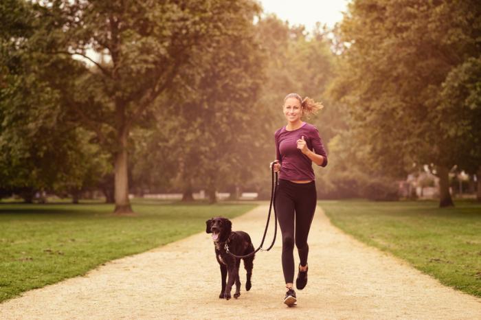 Une femme qui court dans le parc avec son chien
