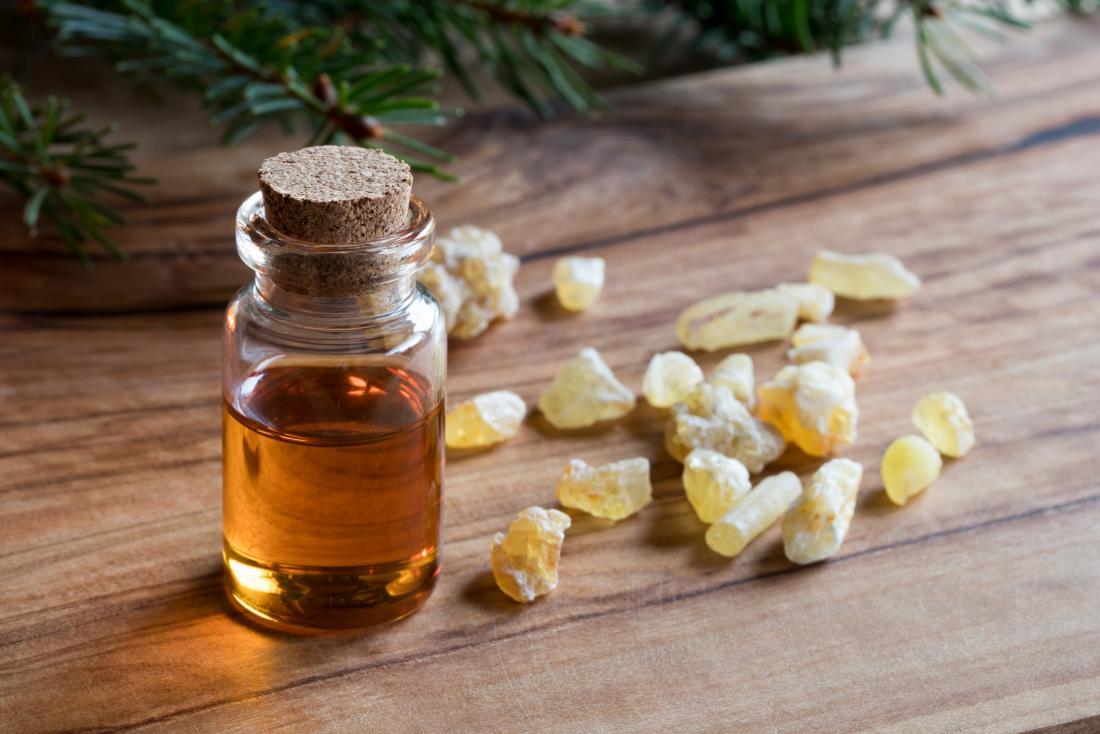 Olio essenziale del franchincenso in bottiglia sulla tavola di legno accanto ai cristalli.