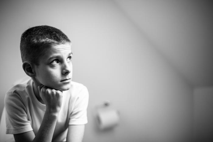 Um jovem rapaz senta-se no banheiro olhando incomodado
