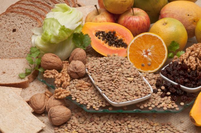 Uma seleção de alimentos ricos em fibras, incluindo nozes, frutas e pão