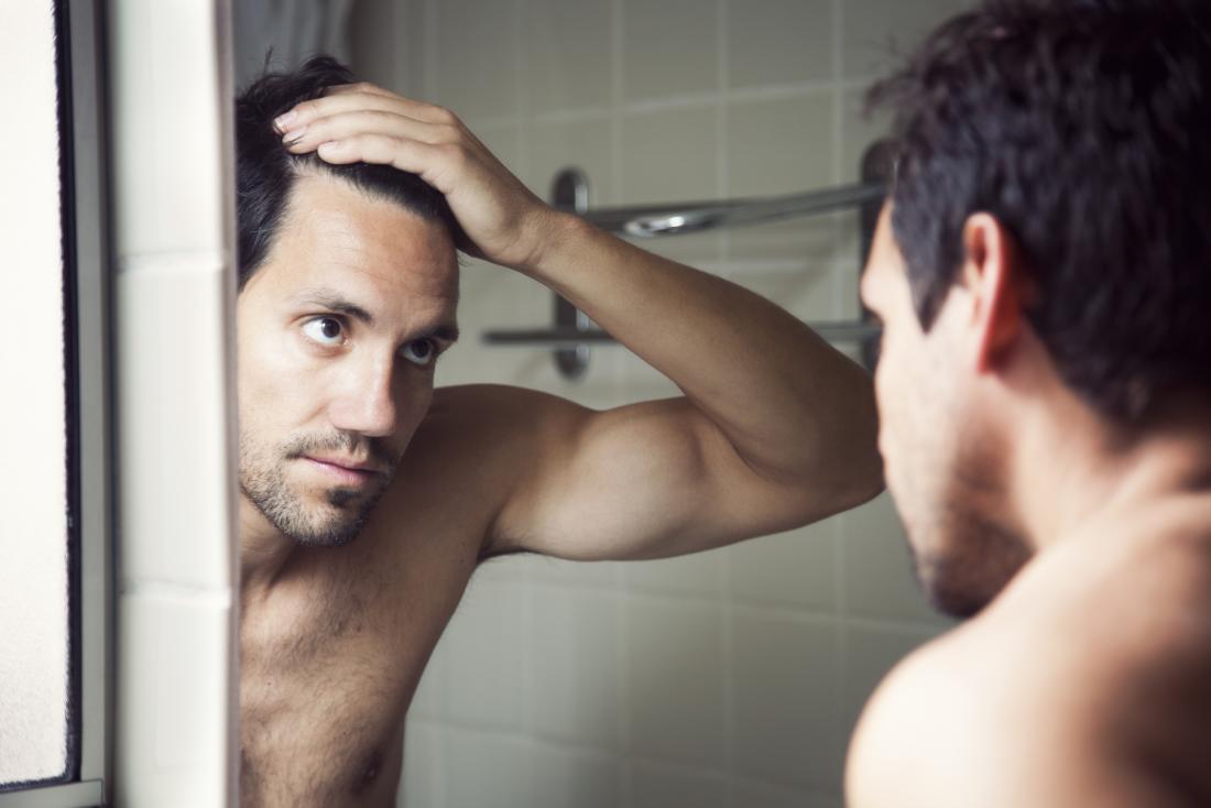 Homem querendo saber se masturbação provoca queda de cabelo, olhando para a linha do cabelo no espelho do banheiro.