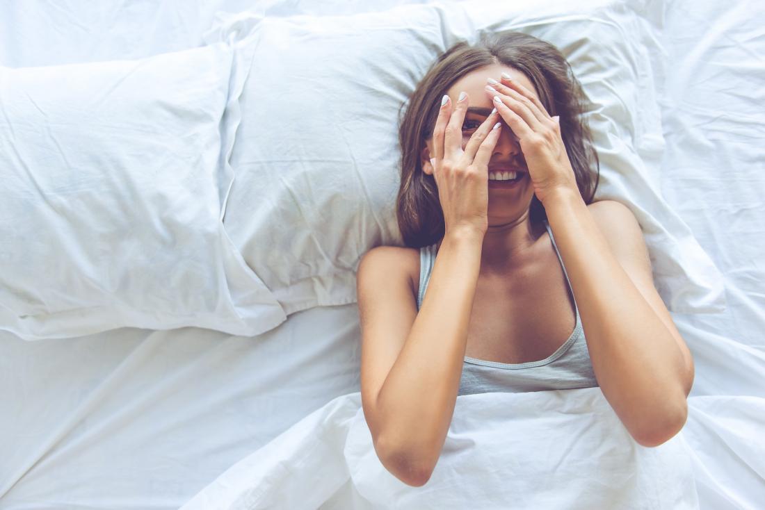 Người phụ nữ cười trên giường