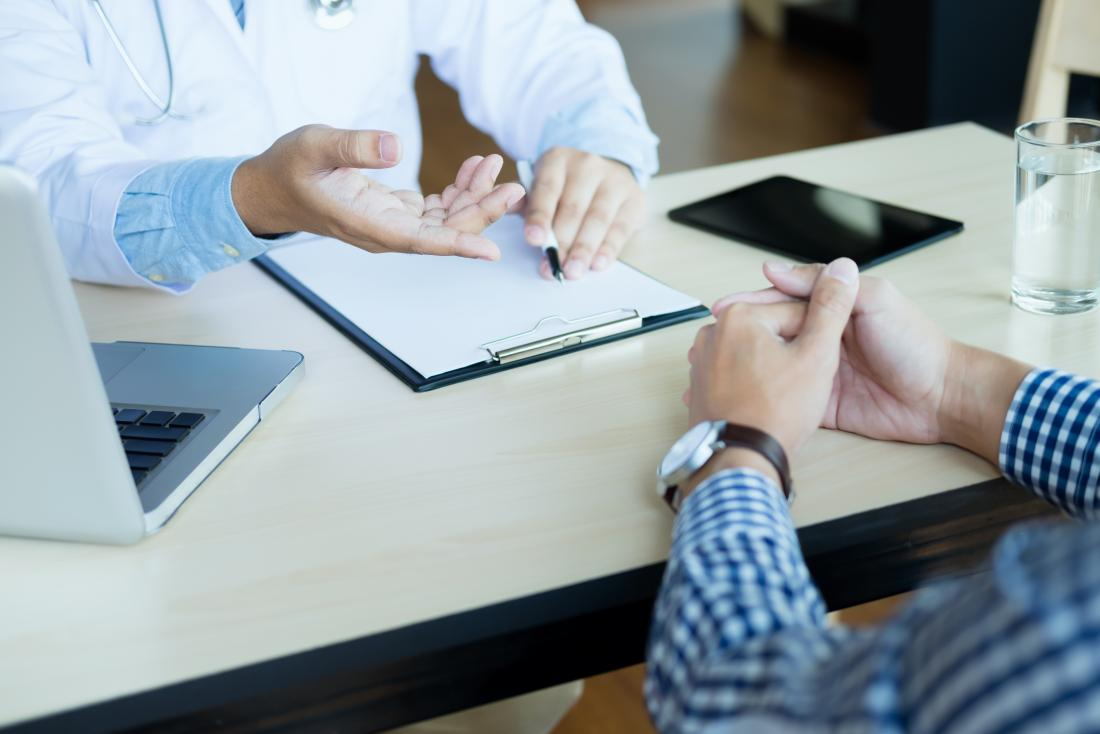 Feche acima do paciente e do doutor cede a mesa com portátil, bloco de notas, e tabuleta.