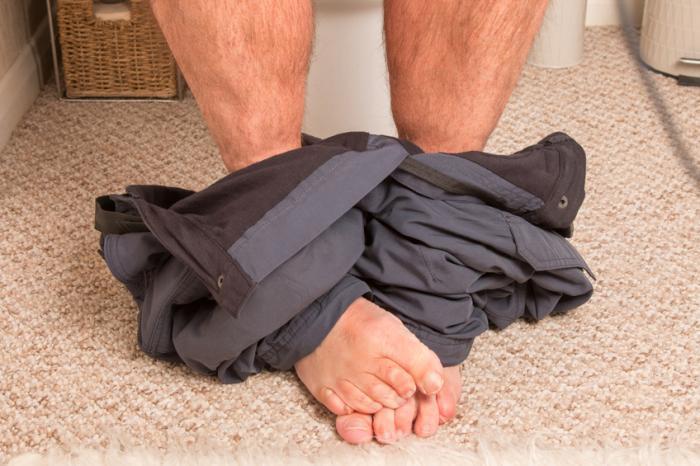 Bàn chân của người ngồi trên nhà vệ sinh.