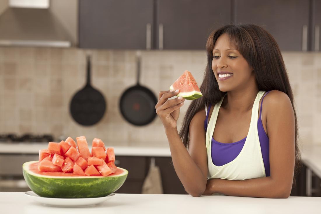 Frau, die ein Stück Wassermelone essend genießt
