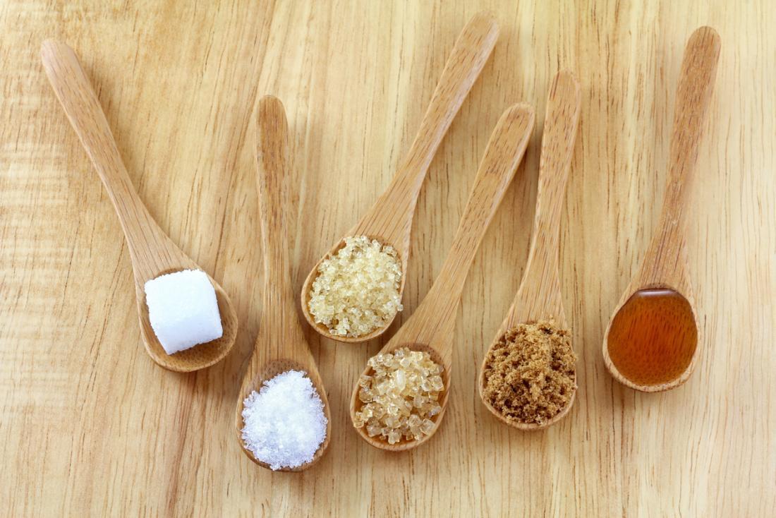 [varietà di zuccheri in mostra in cucchiai di legno]
