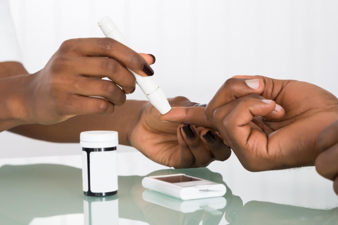 [primo piano delle mani che controllano i livelli di zucchero nel sangue]