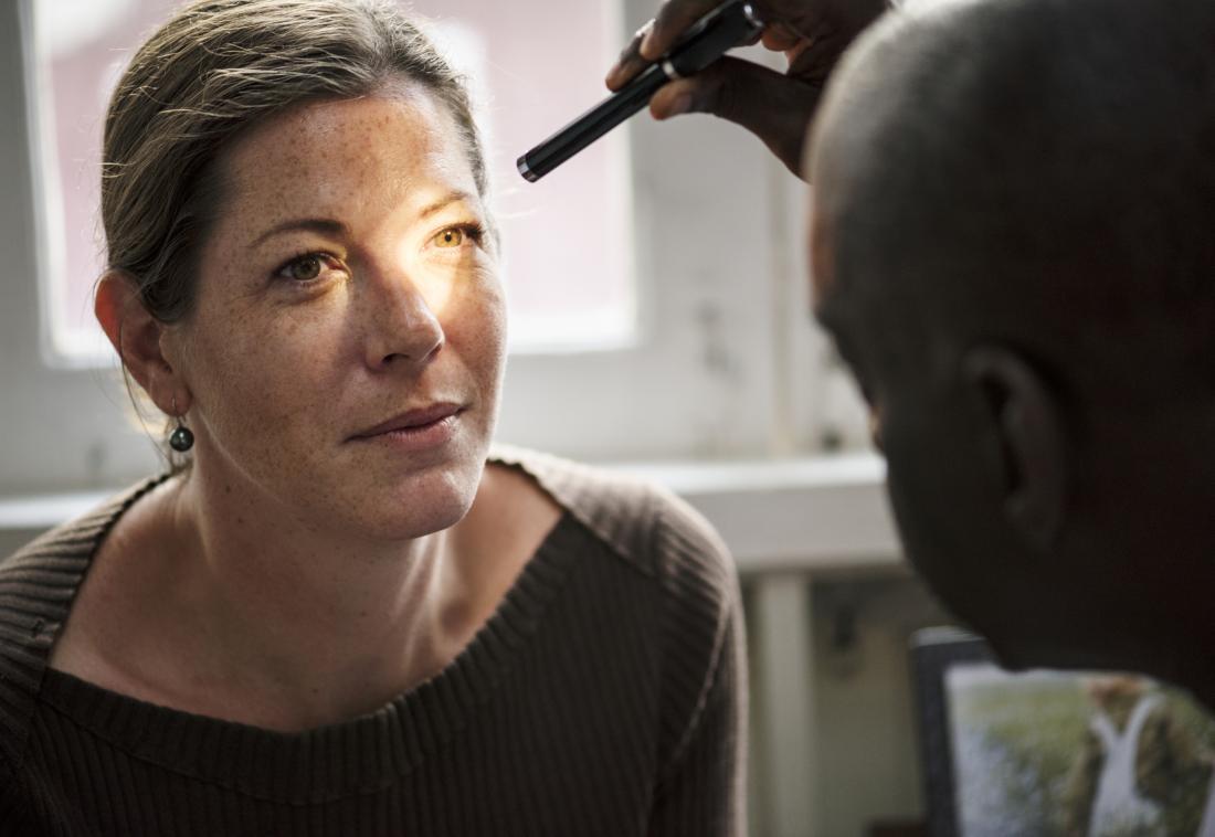 Opticien inspectant l'oeil du patient avec la torche