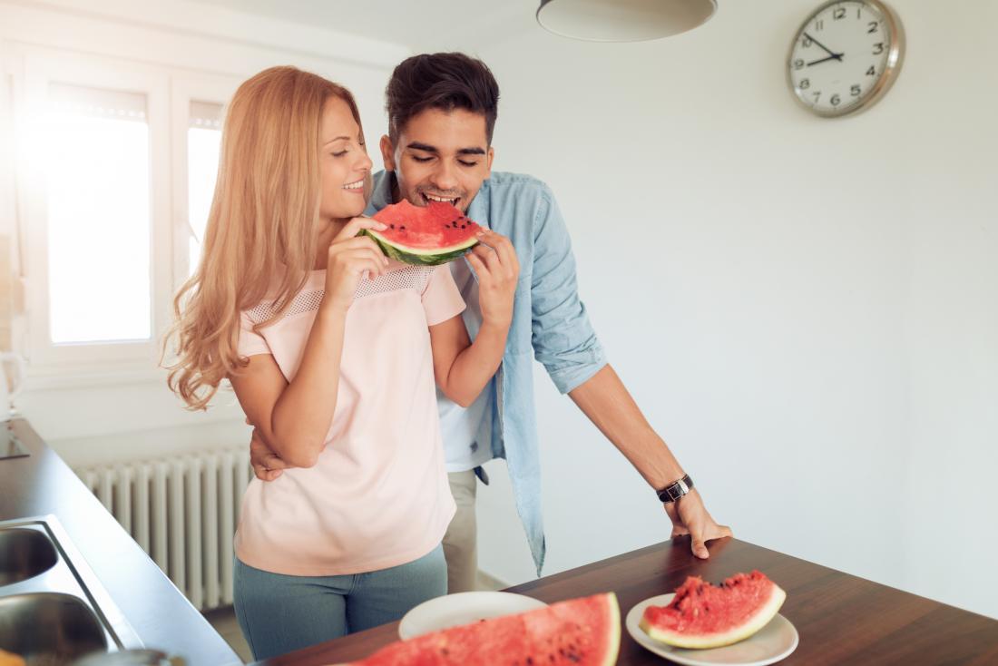 Uomo e donna del viagra dell'anguria che mangiano anguria