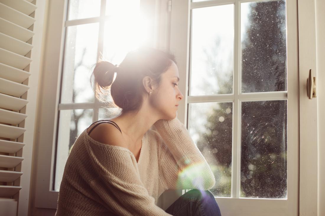 Femme anxieuse regardant par la fenêtre s'inquiéter du cancer de la prostate féminine
