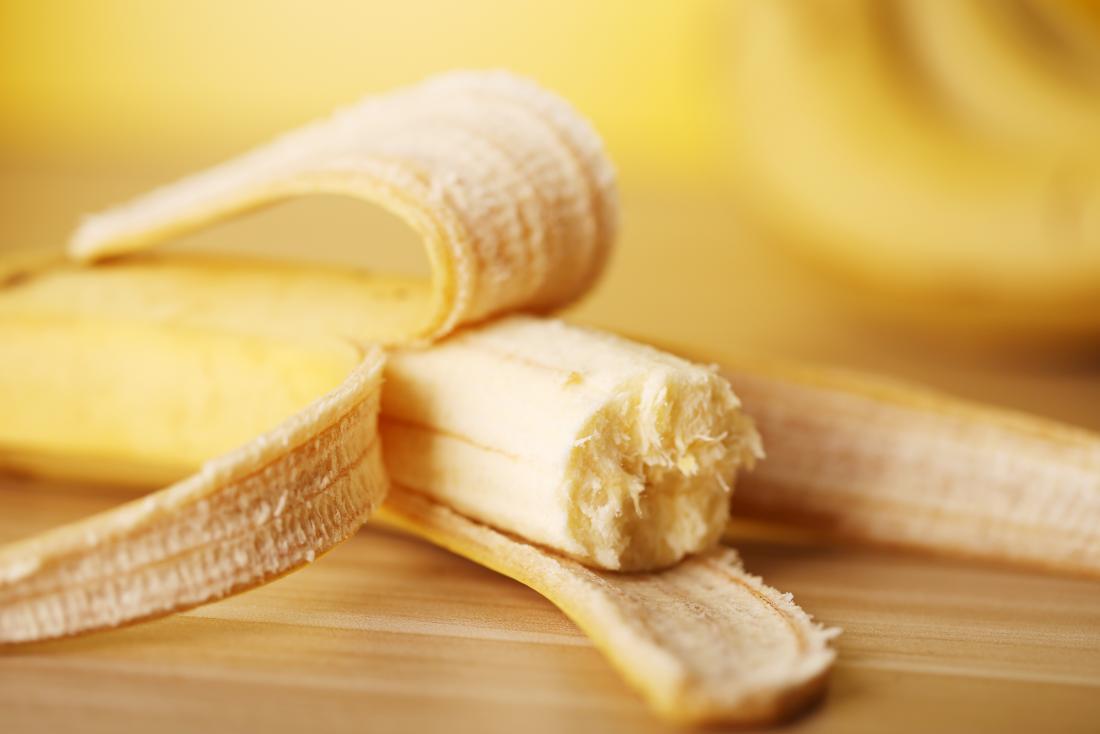 Obrany banan w połowie jedzący na drewnianym stole.