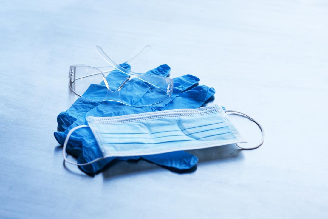 使い捨ての青い手袋、顔面マスク、および保護用ゴーグル。