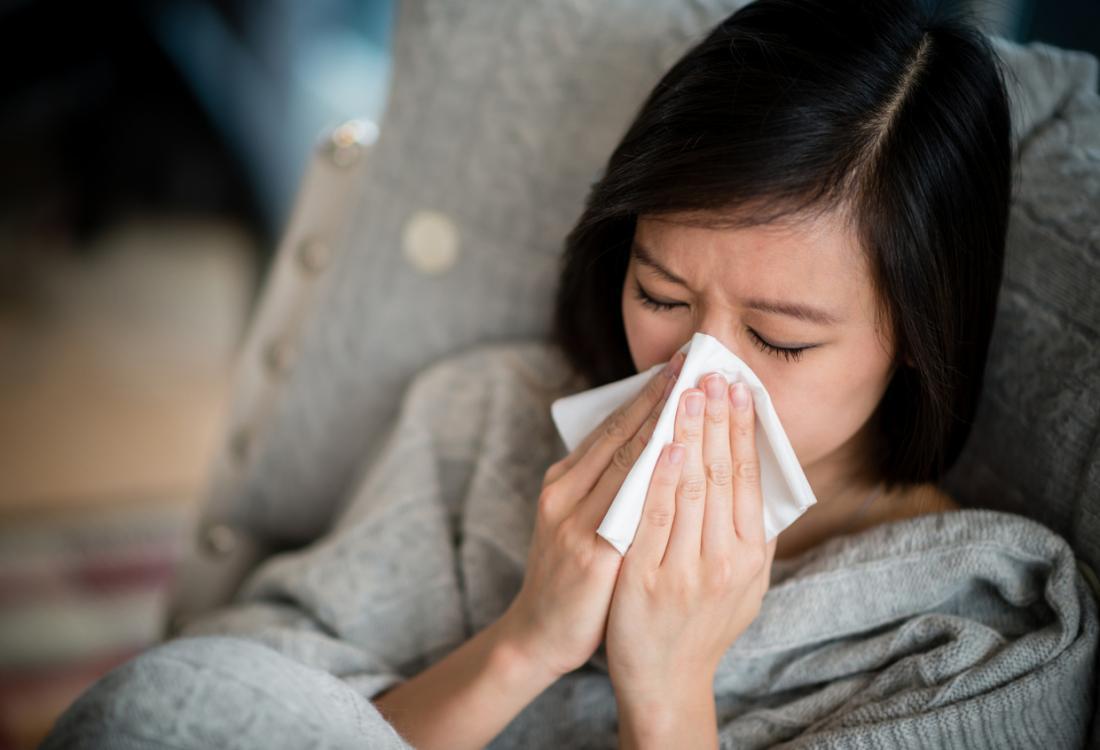 жена издухва носа си