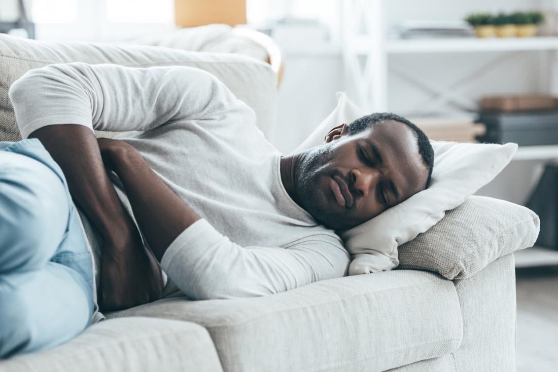 uomo raggomitolato sul divano con mal di stomaco