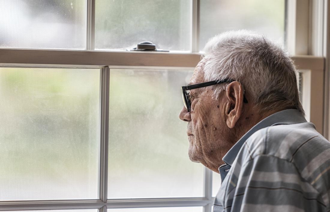 Stary człowiek z demencją patrzeje z okno.