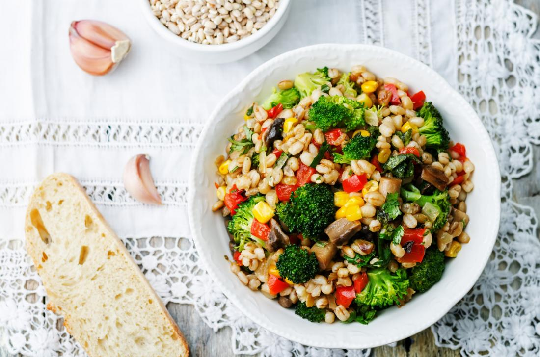 Kasza jęczmienna z kukurydzą, brokułami, czosnkiem, grzybami i papryką w zdrowym wegetariańskim i wegańskim posiłku.