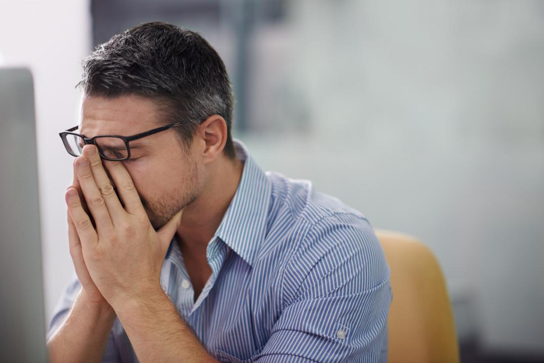 Zestresowany człowiek tarcie most nosa w pracy, zmęczony i zmęczony.