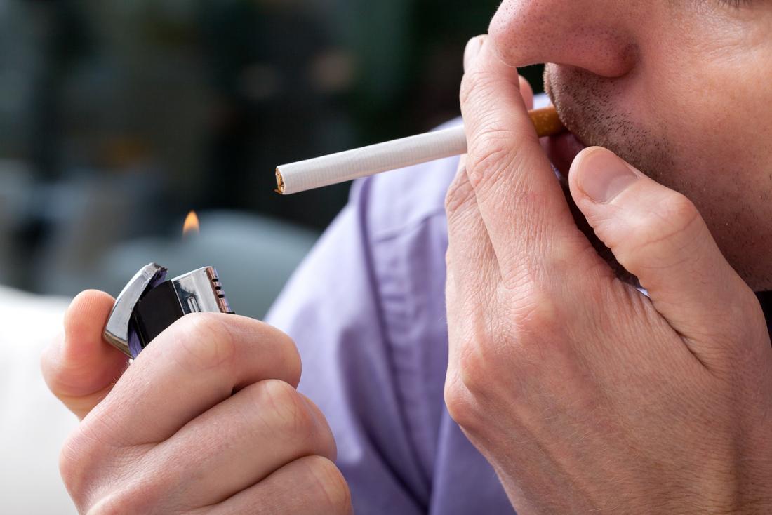 Mann zündet sich eine Zigarette an